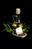 Bottiglia di olio d'oliva, ramo di ulivo, formaggio e pane Fotografie Stock