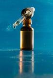 Bottiglia di olio essenziale con gli ambiti di provenienza blu con il contagoccia fotografie stock libere da diritti