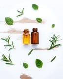 Bottiglia di olio essenziale con salvia di erbe fresca, rosmarino, timo Fotografie Stock