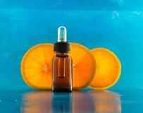 Bottiglia di olio essenziale con tre fette arancio (orizzontale) Fotografie Stock Libere da Diritti