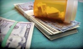 Bottiglia di pillola su molti Americani del dollaro delle banconote immagine stock