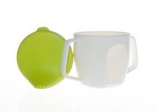 Bottiglia di plastica della tazza per i bambini, la tazza ed il coperchio verde fotografia stock libera da diritti