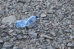 Bottiglia di plastica sulla riva fotografia stock