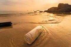 Bottiglia di plastica vuota sulla spiaggia con le onde del mare ad alba di mattina thailand immagine stock libera da diritti
