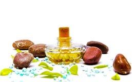 Bottiglia di profumo con i fogli di verde e le pietre rosse Fotografie Stock
