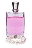 Bottiglia di profumo con un braccialetto della perla su fondo bianco Immagini Stock