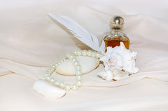 Bottiglia di profumo d'annata con le perle, i crostacei, la pietra del mare bianco e la piuma Fotografia Stock Libera da Diritti
