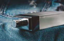 Bottiglia di profumo sui jeans fotografia stock libera da diritti