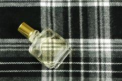 Bottiglia di profumo sul reticolo dell'assegno fotografia stock