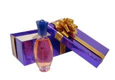 Bottiglia di profumo sulla casella viola sopra priorità bassa bianca Immagine Stock