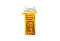 Bottiglia di Rx con una banconota in dollari isolata su un fondo bianco Fotografia Stock