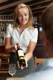 Bottiglia di Showing Restaurant Customer della cameriera di bar di vino rosso fotografia stock libera da diritti