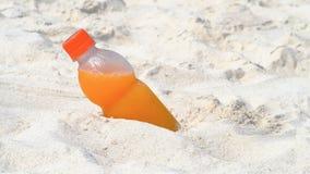Bottiglia di succo d'arancia sulla spiaggia Fotografia Stock