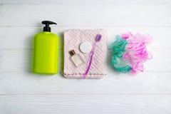 Bottiglia di verde del gel della doccia o dello sciampo con gli accessori della pezzuola per lavare e del bagno dell'asciugamano fotografia stock