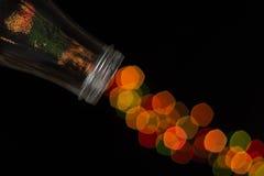 Bottiglia di vetro che rovescia bello bokeh Fotografie Stock