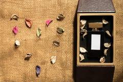 Bottiglia di vetro del profumo dentro il contenitore di regalo dorato immagine stock