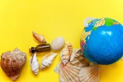 Bottiglia di vetro delle conchiglie, del globo e su un fondo giallo Immagini Stock