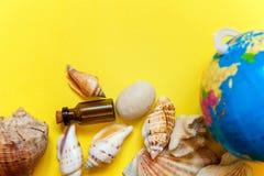 Bottiglia di vetro delle conchiglie, del globo e su un fondo giallo Fotografia Stock