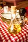 Bottiglia di vetro di olio d'oliva sulla tavola al ristorante Immagini Stock