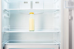 Bottiglia di vetro di yogurt sullo scaffale del frigorifero vuoto aperto immagine stock