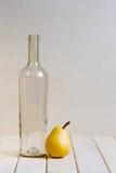 Bottiglia di vetro e pera gialla sulla tavola bianca Fotografie Stock Libere da Diritti