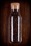 Bottiglia di vetro in pieno dei chicchi di caffè immagine stock