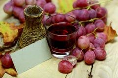 Bottiglia di vimini casalinga ed uva del succo rosso di uva naturale Immagine Stock