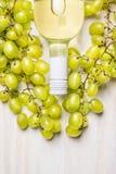 Bottiglia di vino bianco e dell'uva matura su fondo di legno bianco rustico, vista superiore fotografia stock libera da diritti