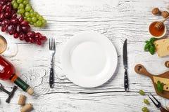 Bottiglia di vino bianco, uva, miele, formaggio, bicchiere di vino, piatto, coltello e forcella sul bordo di legno bianco fotografia stock
