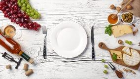 Bottiglia di vino bianco, uva, miele, formaggio, bicchiere di vino, piatto, coltello e forcella sul bordo di legno bianco fotografia stock libera da diritti