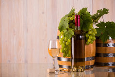 Bottiglia di vino con l'uva e i grapeleaves dei barilotti Fotografie Stock