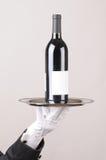 Bottiglia di vino della holding del maggiordomo sul cassetto fotografia stock libera da diritti