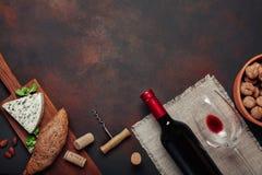 Bottiglia di vino, della noce, del formaggio blu, delle mandorle, della cavaturaccioli e del sughero Fotografie Stock Libere da Diritti