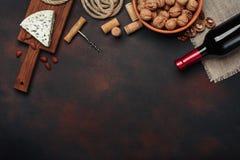 Bottiglia di vino, della noce, delle mandorle, della cavaturaccioli e dei sugheri, sulla b arrugginita Immagini Stock