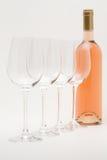 Bottiglia di vino della Rosa con i bicchieri di vino allineati Fotografia Stock Libera da Diritti