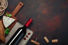 Bottiglia di vino, delle mandorle, della cavaturaccioli e dei sugheri, su backgroun arrugginito Fotografia Stock