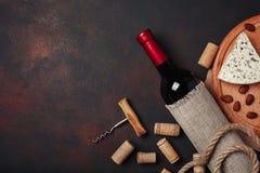 Bottiglia di vino, delle mandorle, della cavaturaccioli e dei sugheri, su backgroun arrugginito Immagini Stock Libere da Diritti