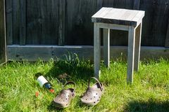 Bottiglia di vino, panchetto e sandali vuoti su erba verde Immagini Stock