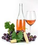 Bottiglia di vino rosato, cavaturaccioli, bicchiere di vino ed uva Immagini Stock