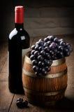Bottiglia di vino rosso, del barilotto e dell'uva Fotografia Stock