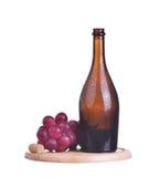 Bottiglia di vino rosso e dell'uva sul piatto di legno isolato su bianco Immagini Stock
