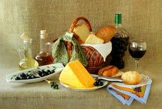 Bottiglia di vino, un canestro di pane, formaggio ed olive Fotografie Stock Libere da Diritti