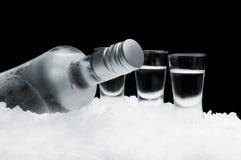Bottiglia di vodka con i vetri che stanno sul ghiaccio su fondo nero Immagini Stock