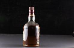 Bottiglia di whiskey con fondo nero Fotografie Stock Libere da Diritti