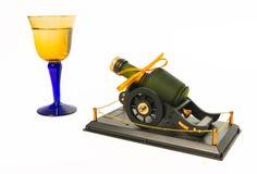 Bottiglia di whiskey verde sulla piattaforma dell'artiglieria con i vetri blu e gialli fotografie stock libere da diritti