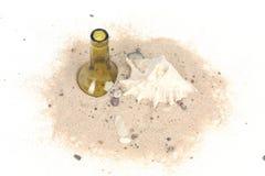 Bottiglia e conchiglia in sabbia della spiaggia su fondo bianco Immagini Stock Libere da Diritti