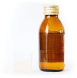 Bottiglia e coppa con medicina Immagine Stock Libera da Diritti