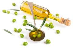 Bottiglia e cucchiaio di olio d'oliva, olive verdi Fotografia Stock Libera da Diritti