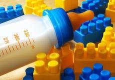 Bottiglia e giocattoli di bambino Fotografie Stock Libere da Diritti