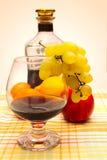 Bottiglia e vetro con il mazzo del vino di uva Immagine Stock